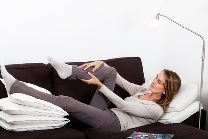 femme qui a mal la jambe allonge